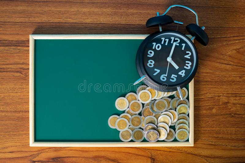Alarm clock and step of coins stacks on working table, time for savings money concept stock images