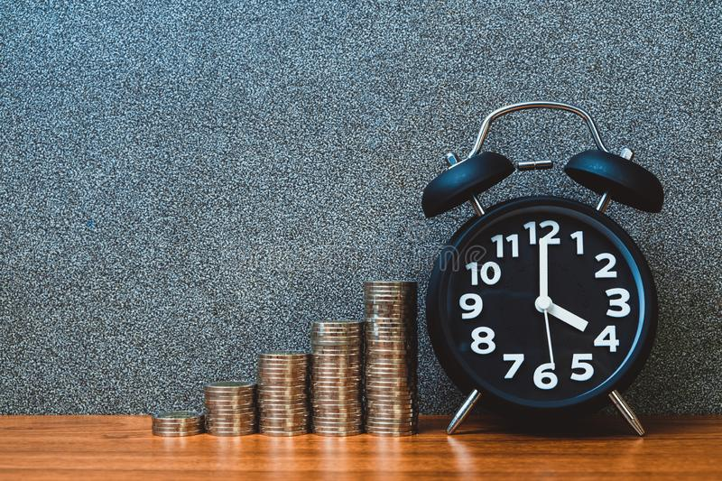 Alarm clock and step of coins stacks on working table, time for savings money concept royalty free stock photo