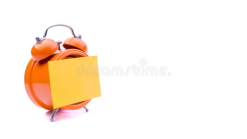 Alarm clock with sticky note on white background. stock photography