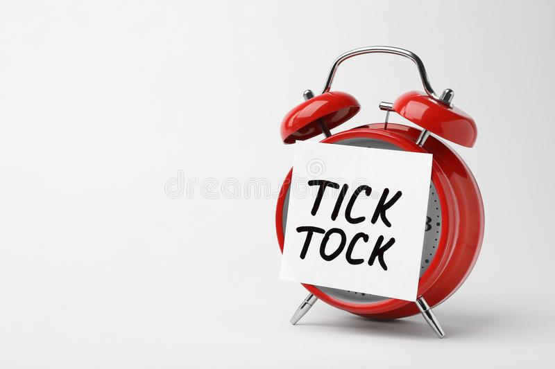 Alarm clock and sticky note with words TICK TOCK stock photography