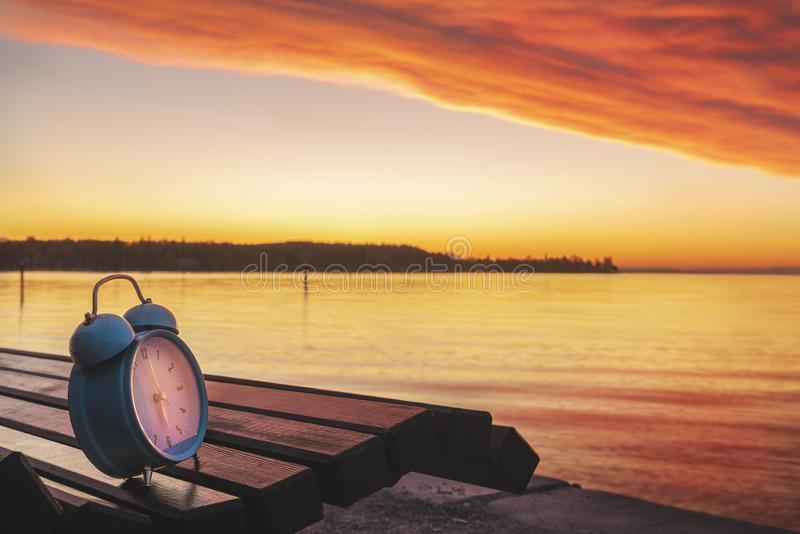 Alarm clock and sunrise over Lake Constance. Alarm clock on a wooden bench on the shores of Lake Constance, at sunrise, in Konstanz, Germany. Early morning. Wake stock photos