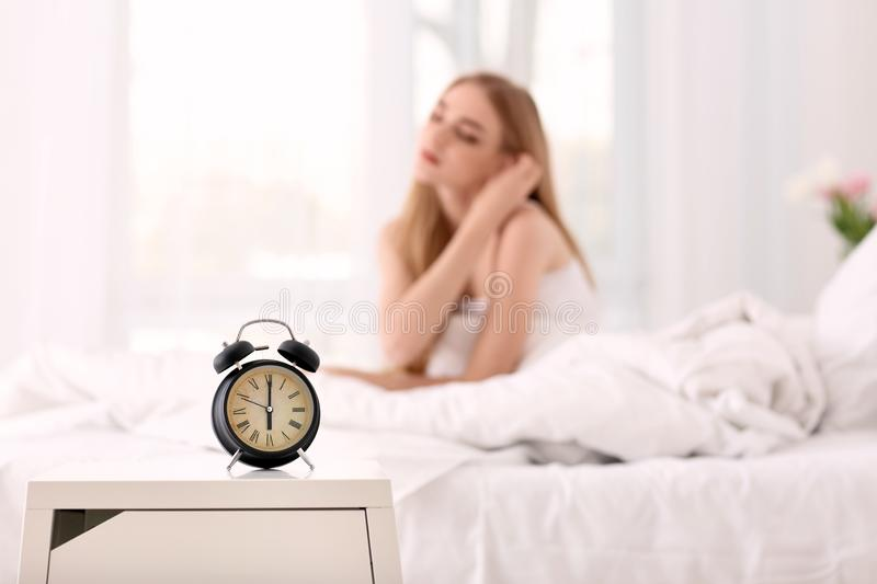 Alarm clock on table in bedroom of beautiful woman. Morning time royalty free stock image