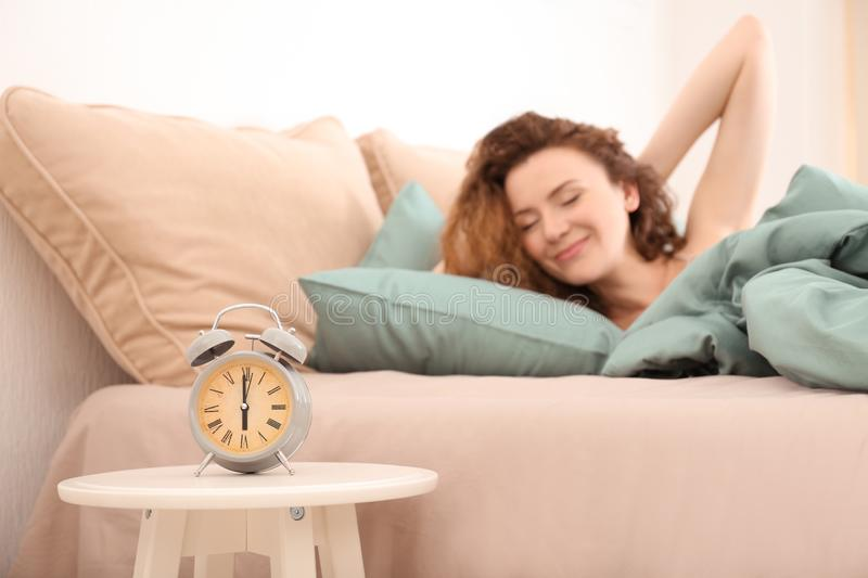 Alarm clock on table in bedroom of beautiful woman. Morning time royalty free stock photos