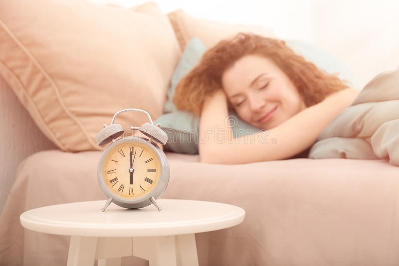Alarm clock on table in bedroom of beautiful woman. Morning time stock photography