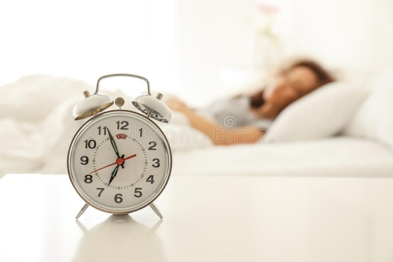 Alarm clock on table in bedroom of beautiful young woman. Morning time stock image