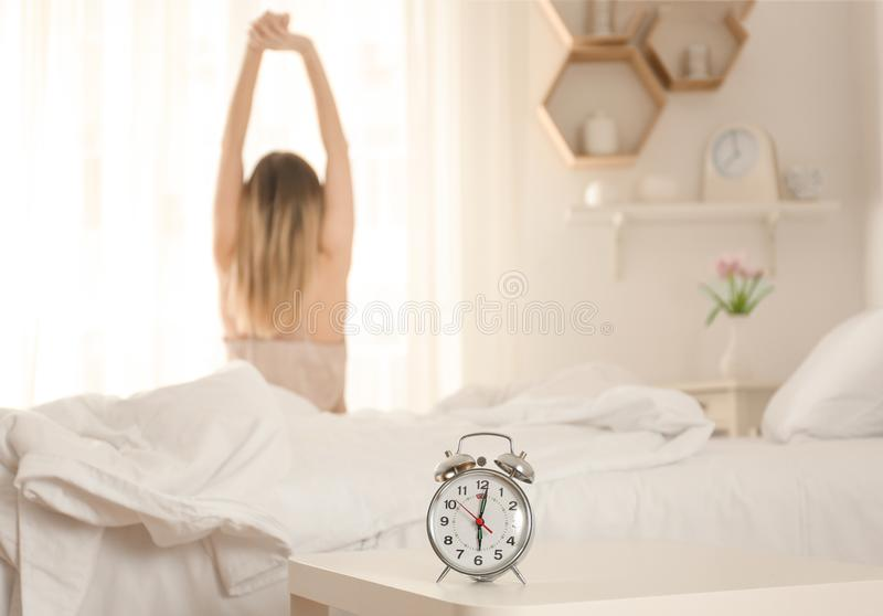 Alarm clock on table in bedroom of beautiful young woman. Morning time stock photos