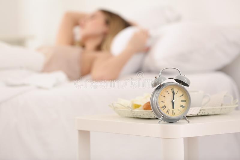 Alarm clock on table in bedroom of beautiful young woman. Morning time royalty free stock images