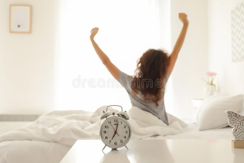 Alarm clock on table in bedroom of beautiful young woman. Morning time stock images