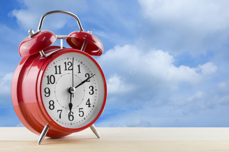 Download Alarm Clock On The Table With Blue Sky Background Stock Photo - Image: 83708185