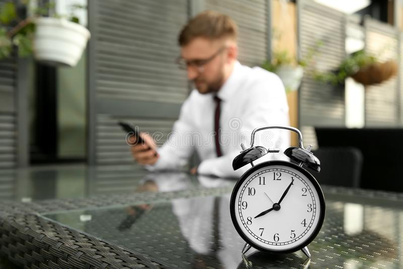 Alarm clock on table of businessman resting in cafe royalty free stock photo