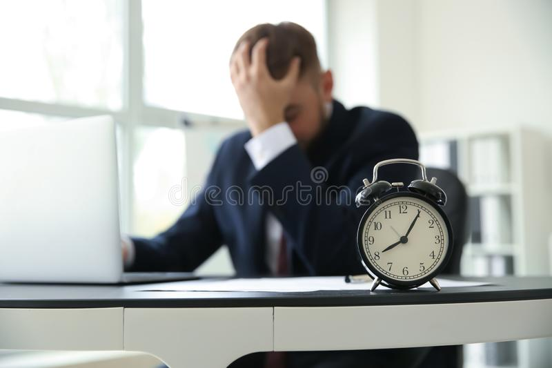 Alarm clock on table of emotional businessman in office royalty free stock images
