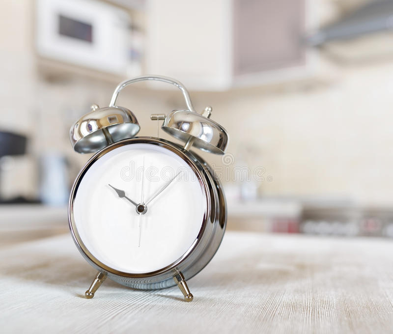 Alarm clock on a table in the kitchen stock photography