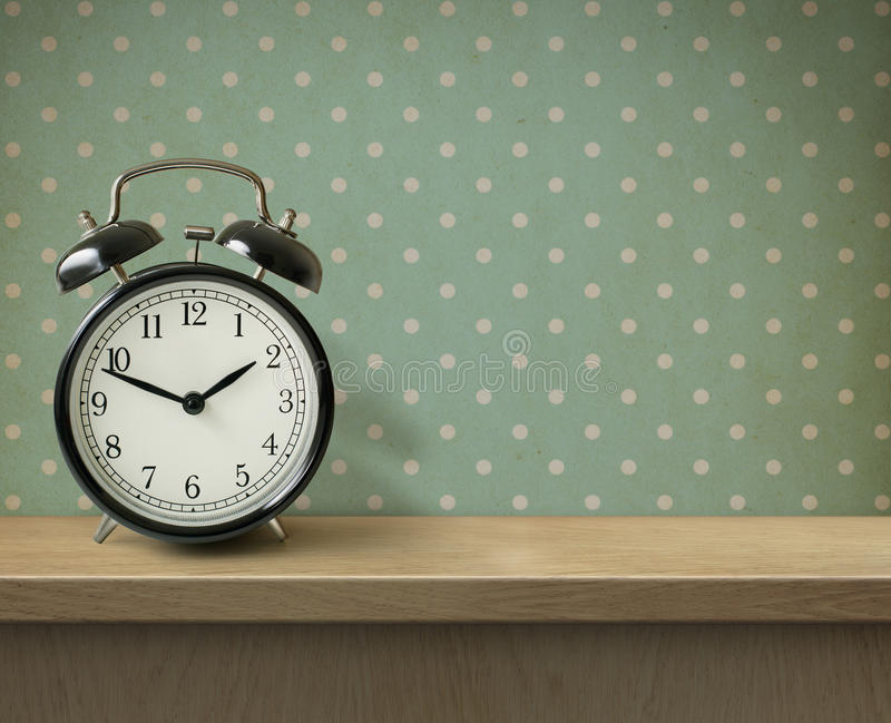 Alarm clock on table or shelf background. Retro alarm clock on table or shelf stock images