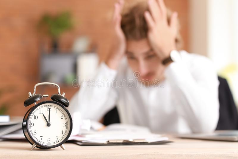 Alarm clock on table of stressed businessman missing deadlines stock photography