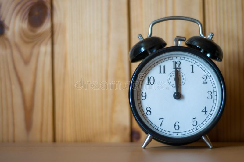 Alarm clock on table. Time. Planing. Hour. Watch. Numbers on clock face royalty free stock photo