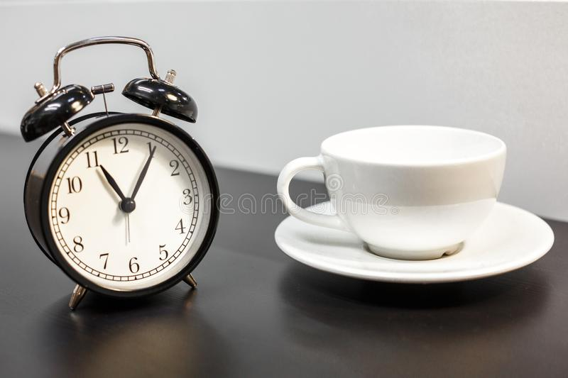 Alarm clock on the table and white mug, tea time, rest concept stock photography