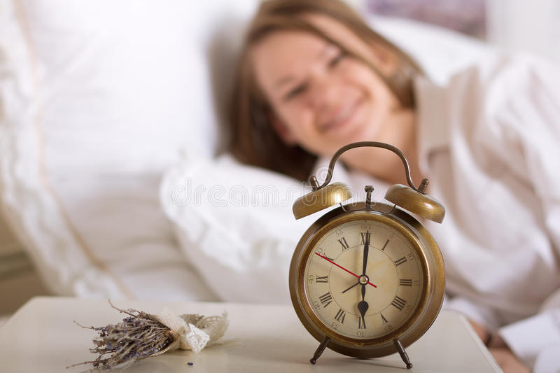 Alarm Clock On Table And Woman Sleeping Royalty Free Stock Images