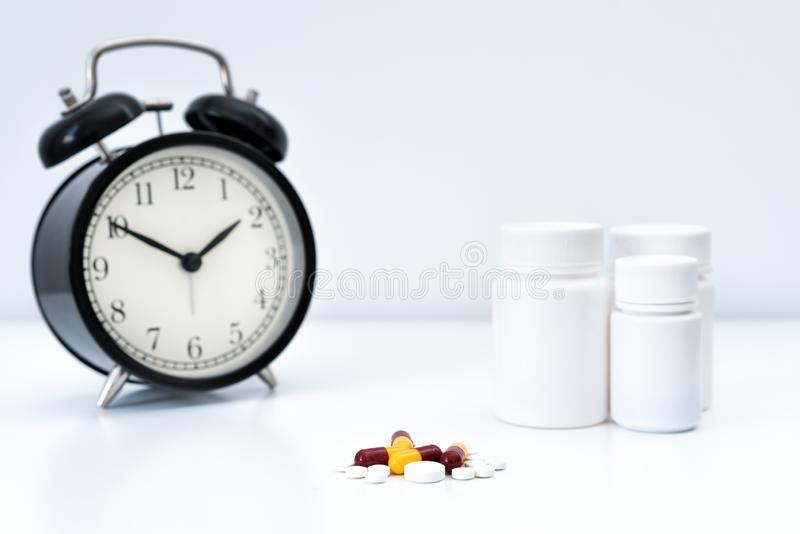 Alarm clock tablet capsules and a glass of water stock photography