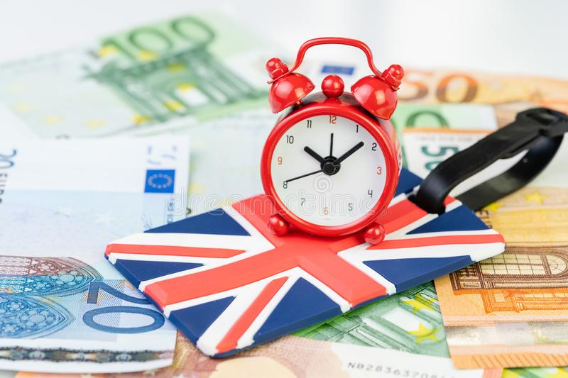 Alarm clock on Union jack, United Kingdom national flag luggage label on Euro banknotes using as countdown on Brexit England royalty free stock photography