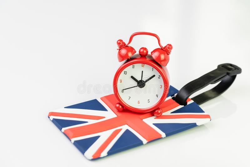 Alarm clock on Union jack, United Kingdom national flag luggage label using as countdown on Brexit England withdrawal from Euro stock image
