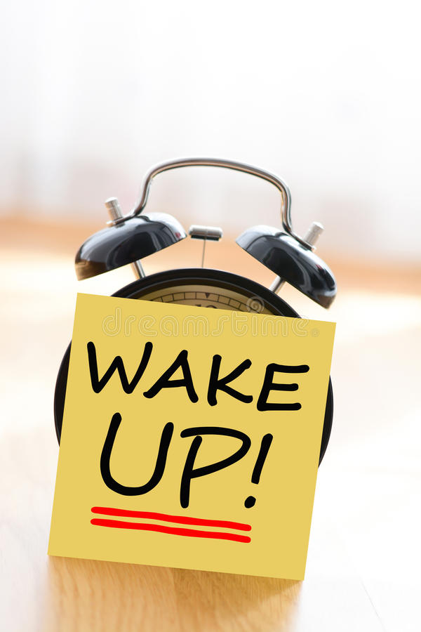 Alarm clock with wake up adhesive note royalty free stock image