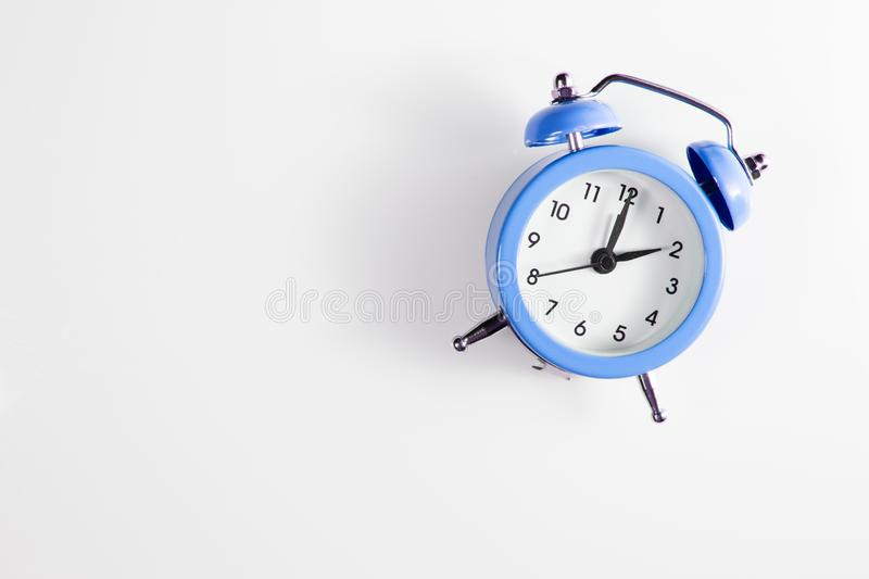 Alarm clock on a white background with shadows. Two o`clock in the afternoon. View from above. Space for text royalty free stock images