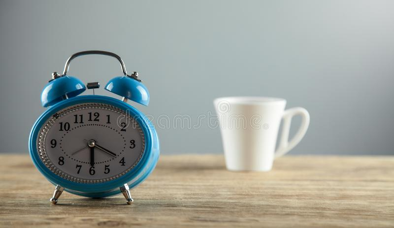 Alarm clock and white coffee cup on the wooden desk royalty free stock image