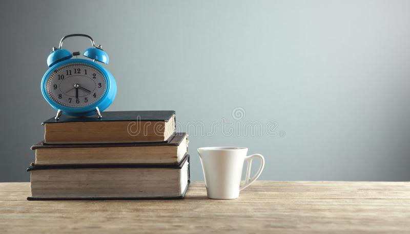 Alarm clock and white coffee cup on the wooden desk stock image