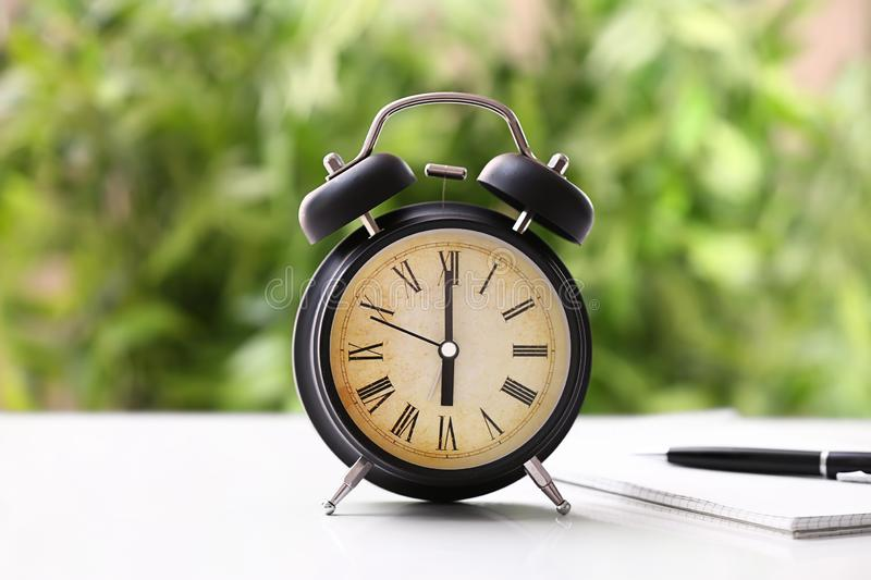 Alarm clock on white table outdoors stock image