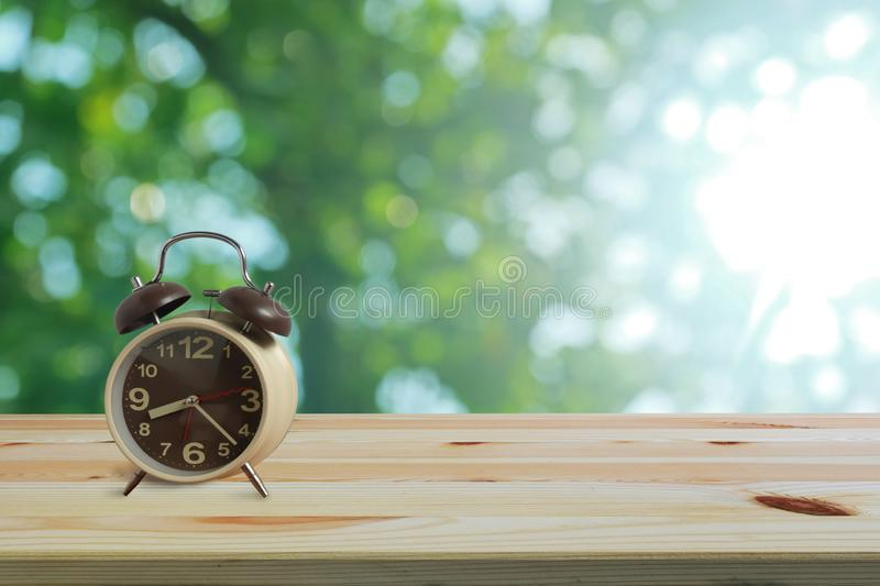 Alarm clock on wooden floor and green bokeh background with copy space, Morning wake up is bright air of nature royalty free stock photos