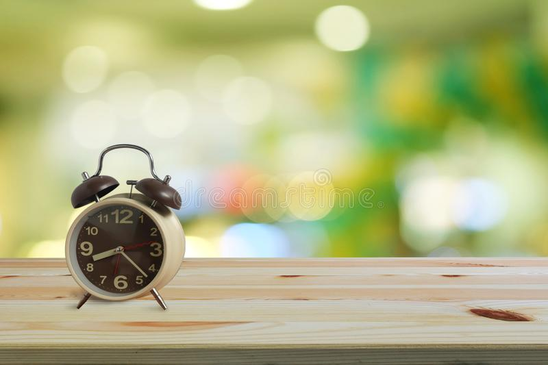 Alarm clock on wooden floor and green bokeh background with copy space, Morning wake up is bright air of nature stock photos