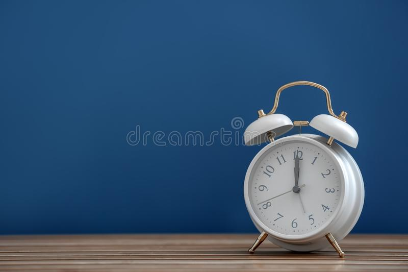 Alarm clock on wooden table against color background stock photos