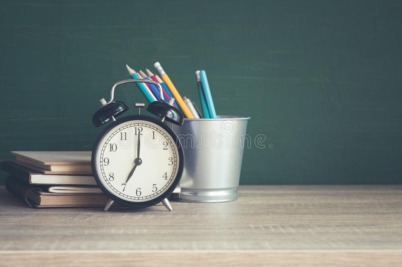 Alarm clock on wooden table on blackboard background in classroom,back to school concept royalty free stock image