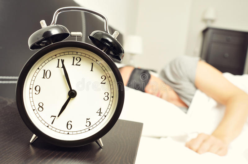 Alarm clock and young man sleeping in bed with a sleep mask stock images