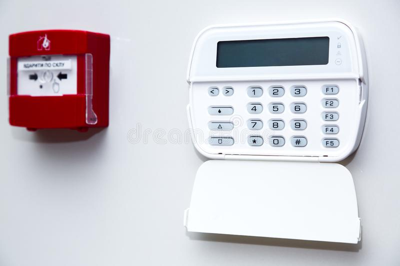 Alarm control panel and fire button. Alarm control panel and fire button on a light gray wall, close-up of the security password entry system to activate and royalty free stock photo