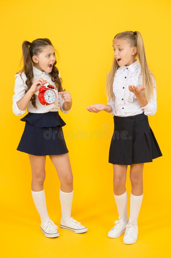 Alarm ringing. Time for lunch. School schedule. Schoolgirls and alarm clock. Children school pupils adorable formal. Uniform outfit. Kids hold alarm clock stock image
