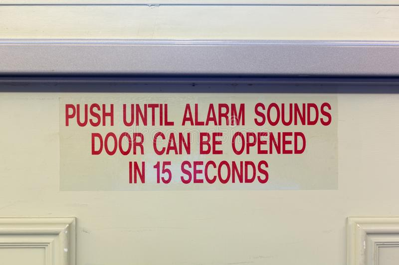 Alarm warning on a door. Bright red lettering of a door alarm with a metal push bar above the sign royalty free stock photography