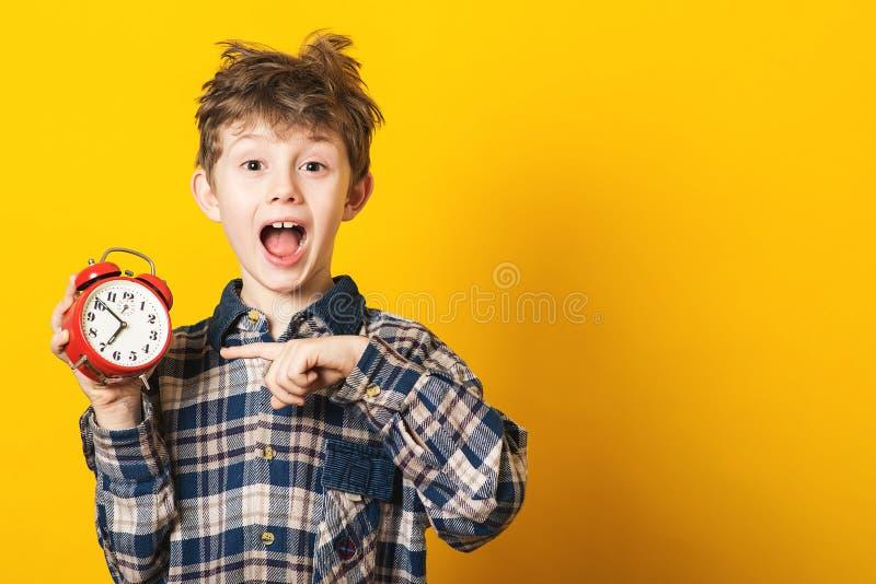 Alarma chocada del reloj de la tenencia del muchacho del niño, espacio de la copia Niño aislado sobre fondo amarillo Hora para la fotos de archivo