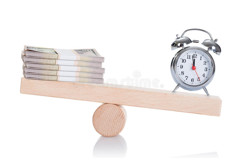 Alarmclock and dollar bundles balancing on seesaw royalty free stock image