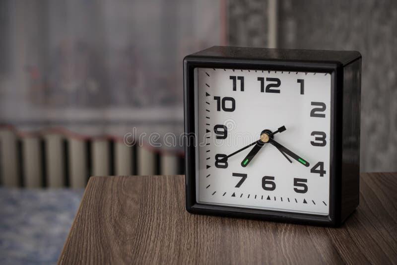 Alarme preto do pulso de disparo em uma tabela de cabeceira em um fundo da cama e da janela imagens de stock