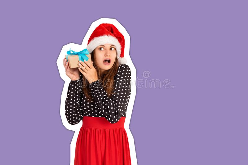 Alarmed girl with her gift listens to what`s in the box. Magazine collage style with trendy color background. holidays concept.  royalty free stock image