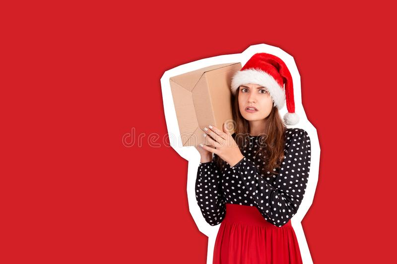 Alarmed girl with her gift listens to what`s in the box. Magazine collage style with trendy color background. holidays concept.  stock photos