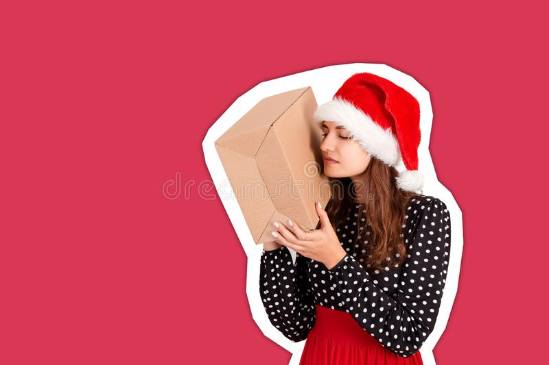 Alarmed girl with her gift listens to what`s in the box. Magazine collage style with trendy color background. holidays concept.  stock images