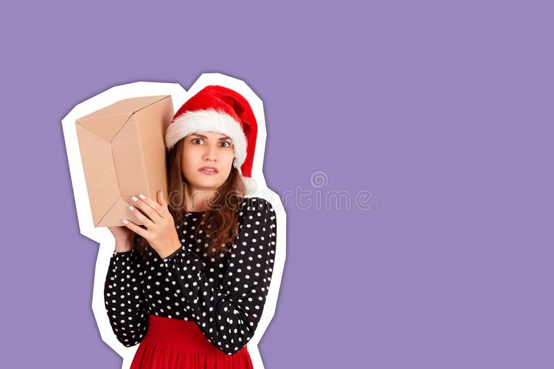 Alarmed girl with her gift listens to what`s in the box. Magazine collage style with trendy color background. holidays concept.  royalty free stock images