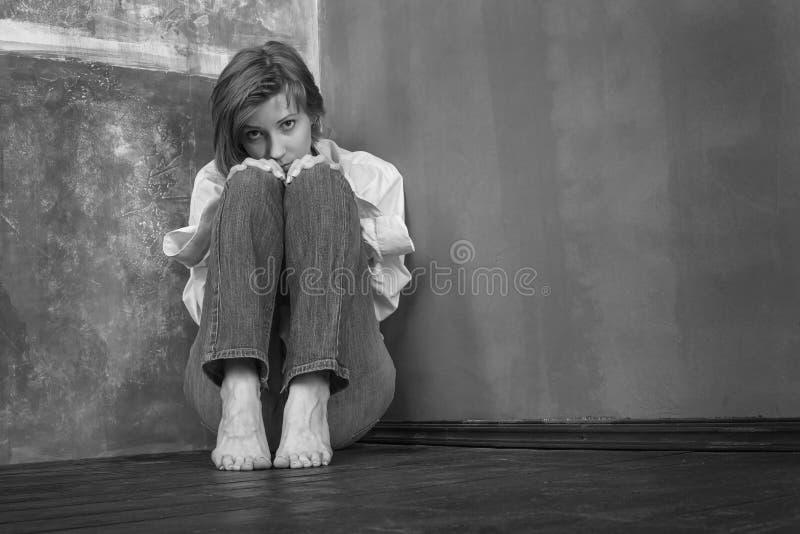 Alarmerad kvinna som sitter på golvet royaltyfria bilder