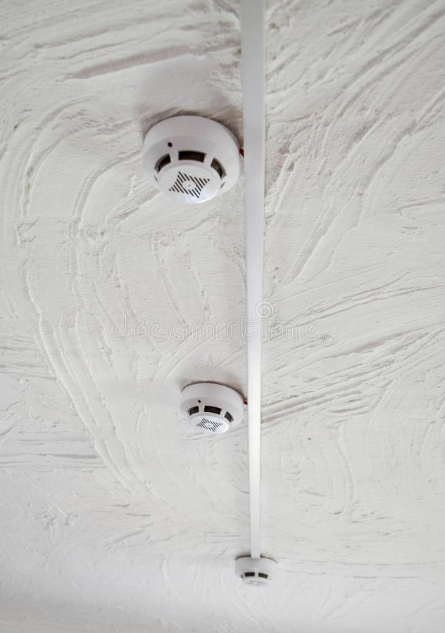 Alarmes d'incendie sur le plafond homme contrôlant l'extincteur image stock