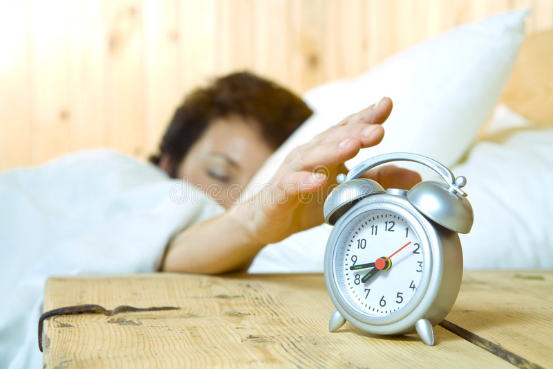 Alarming. Close up view of table clock and woman sleeping on back royalty free stock photos