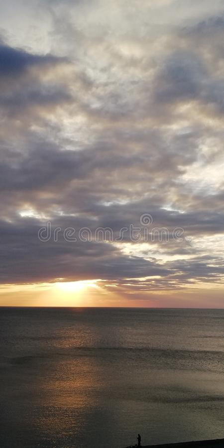Alarming background. Autumn sunset seascape. Clouds, sea and setting sun. The autumn severe dark sea is illuminated by the setting sun, peeking through dense royalty free stock image