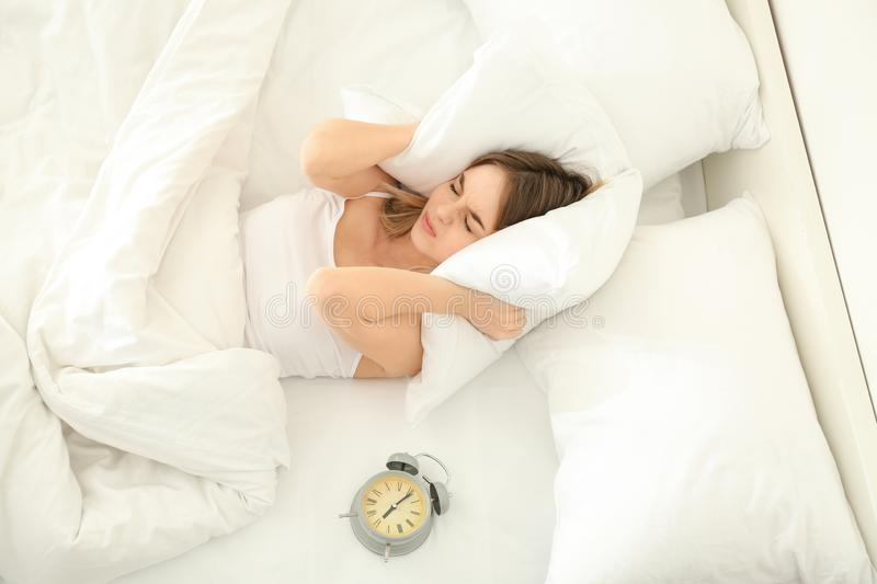 Alarming clock and irritated woman covering her ears with pillow in bed. Morning time royalty free stock image
