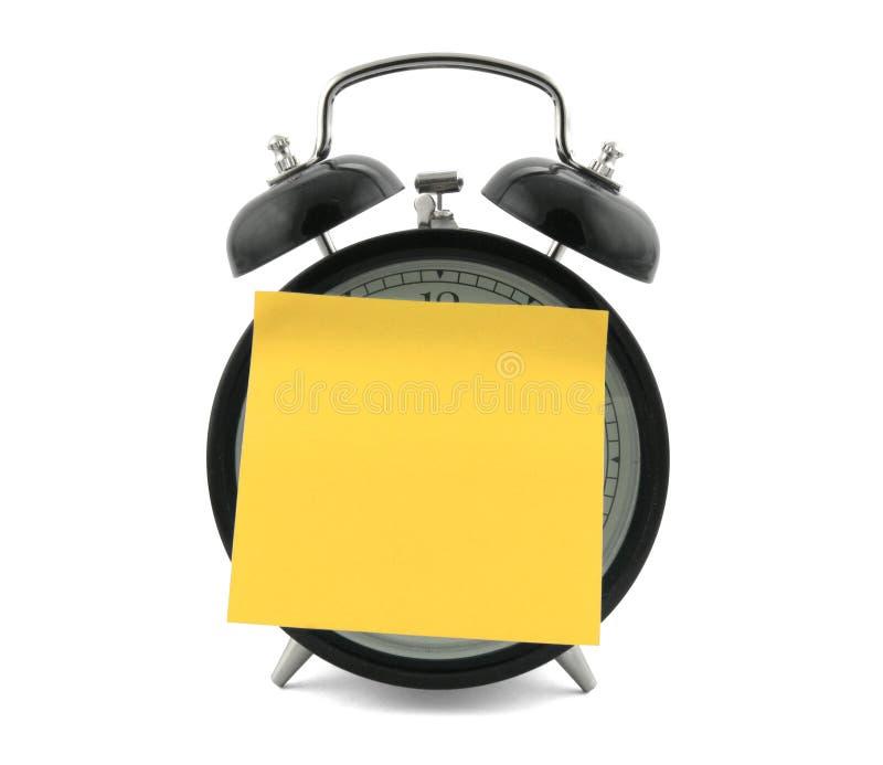 Alarmuhr mit einer Anmerkung lizenzfreies stockbild